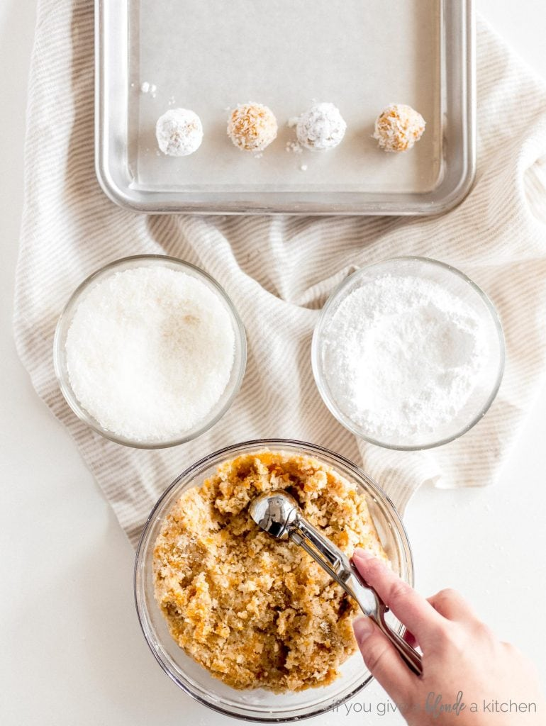 hand holding cookie scoop to scoop coconut apricot mixture. Bowls of shredded coconut and powdered sugar recipe step
