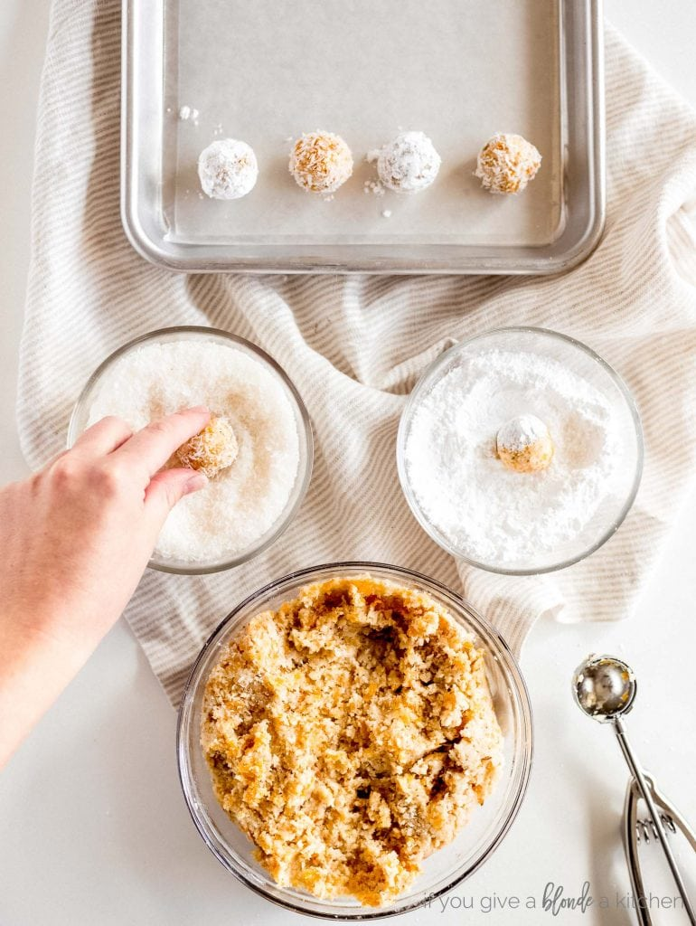 hand rolling coconut apricot ball in bowl of powdered sugar recipe step