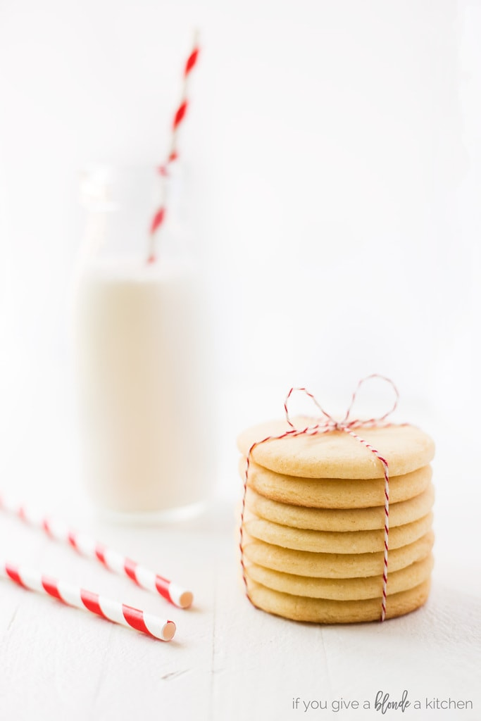 Easy cut out sugar cookie recipe stack of cookies in twine with milk bottle and red striped straws