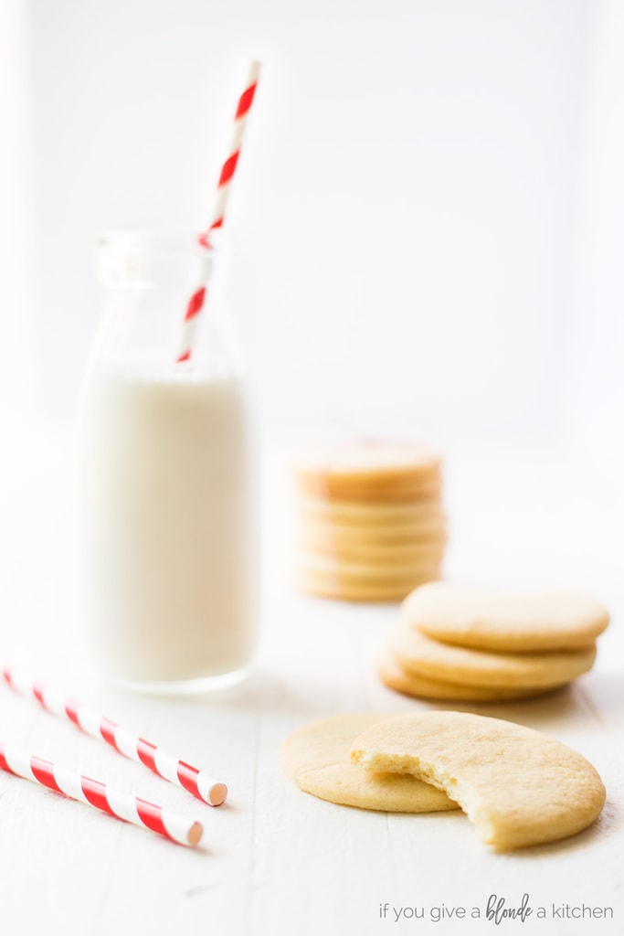 Easy cut out sugar cookie recipe scattered cookies around bottle of milk with red striped straw