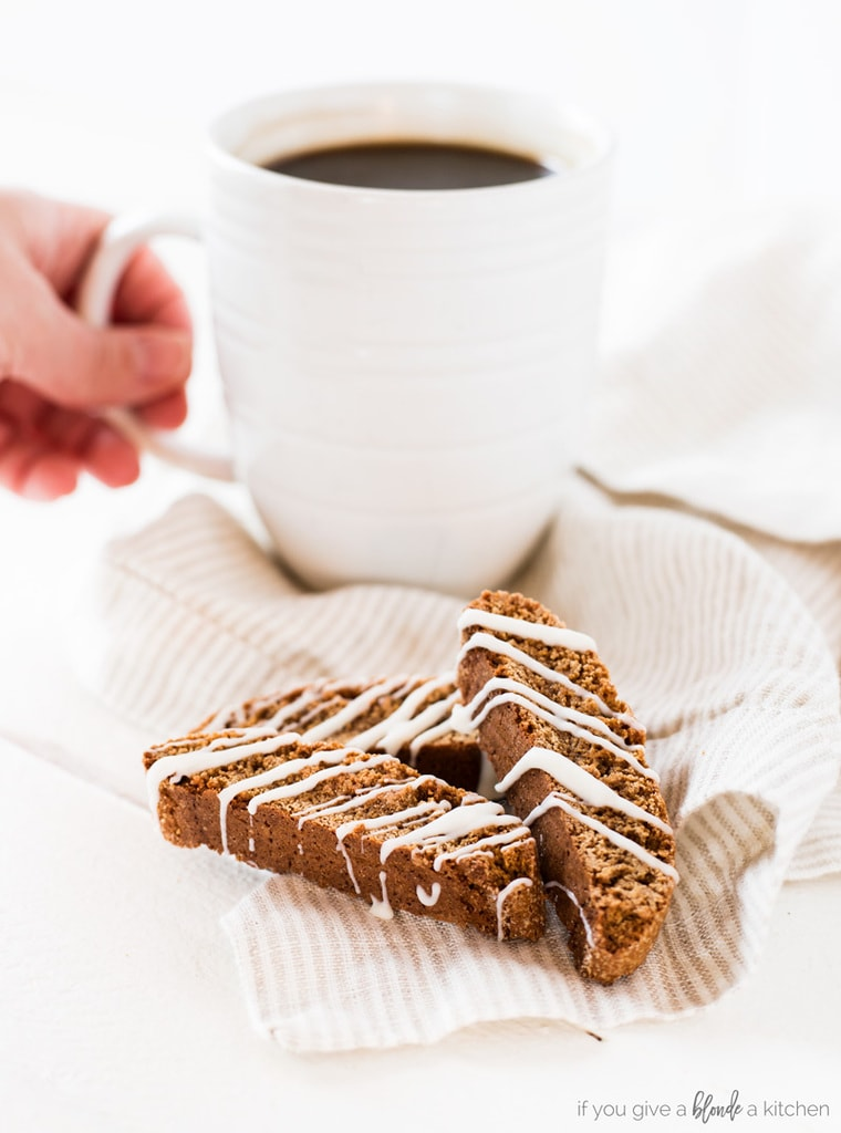 Gingerbread biscotti recipe with white chocolate drizzle and hand reaching for morning coffee