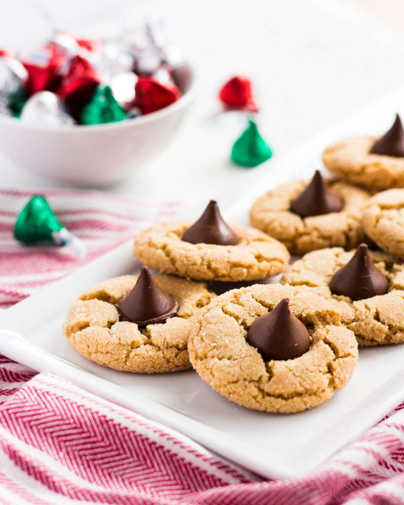This peanut butter blossoms recipe is the perfect combo of peanut butter and chocolate. Each cookie is pressed with a chocolate kiss. | www.ifyougiveablondeakitchen.com