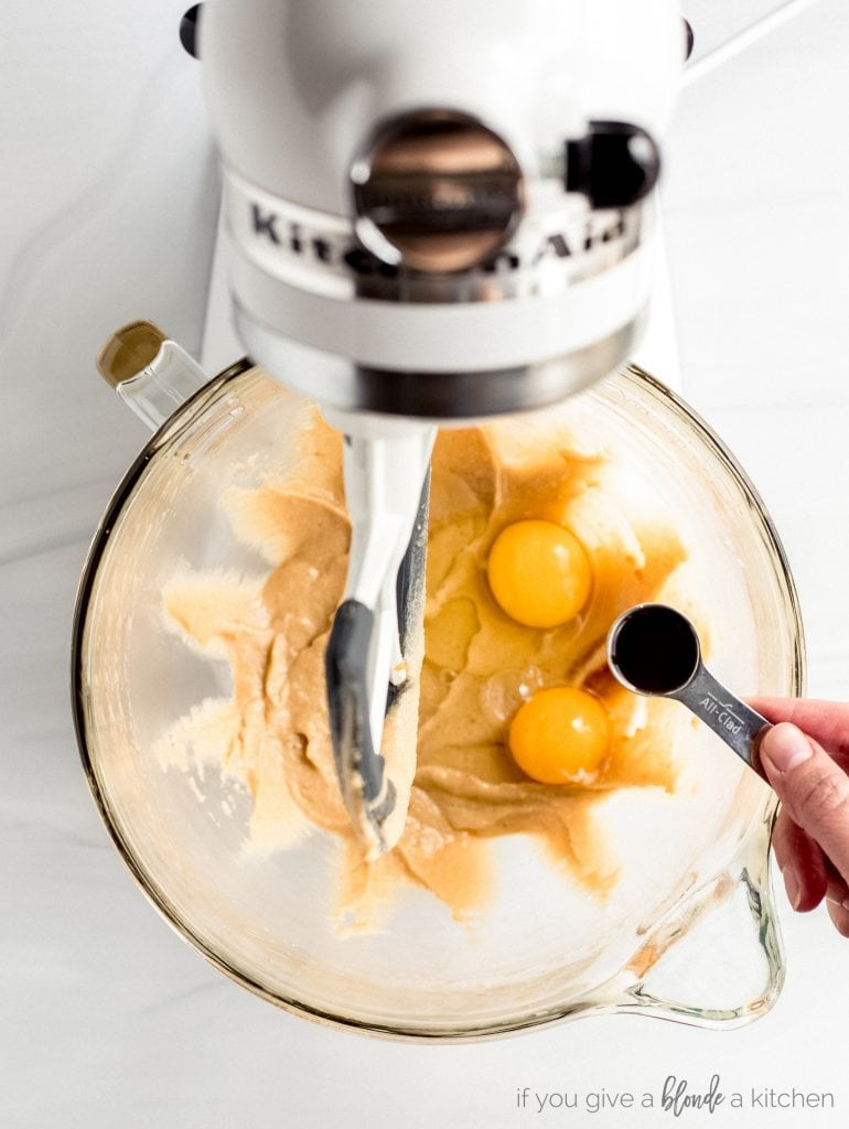 hand holding teaspoon of vanilla extract, stand mixer bowl of sugar, butter, eggs