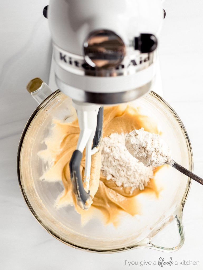spoon of flour added to bowl of stand mixer