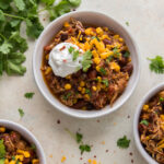 crock pot chicken chili in bowls topped with sour cream and cheese