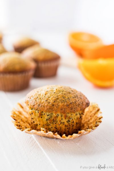 Orange poppy seed muffin on paper wrapper with oranges and muffins in the background