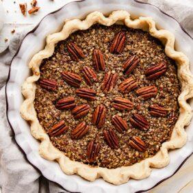 pecan pie in ceramic pie dish with pecan halves arranged on top