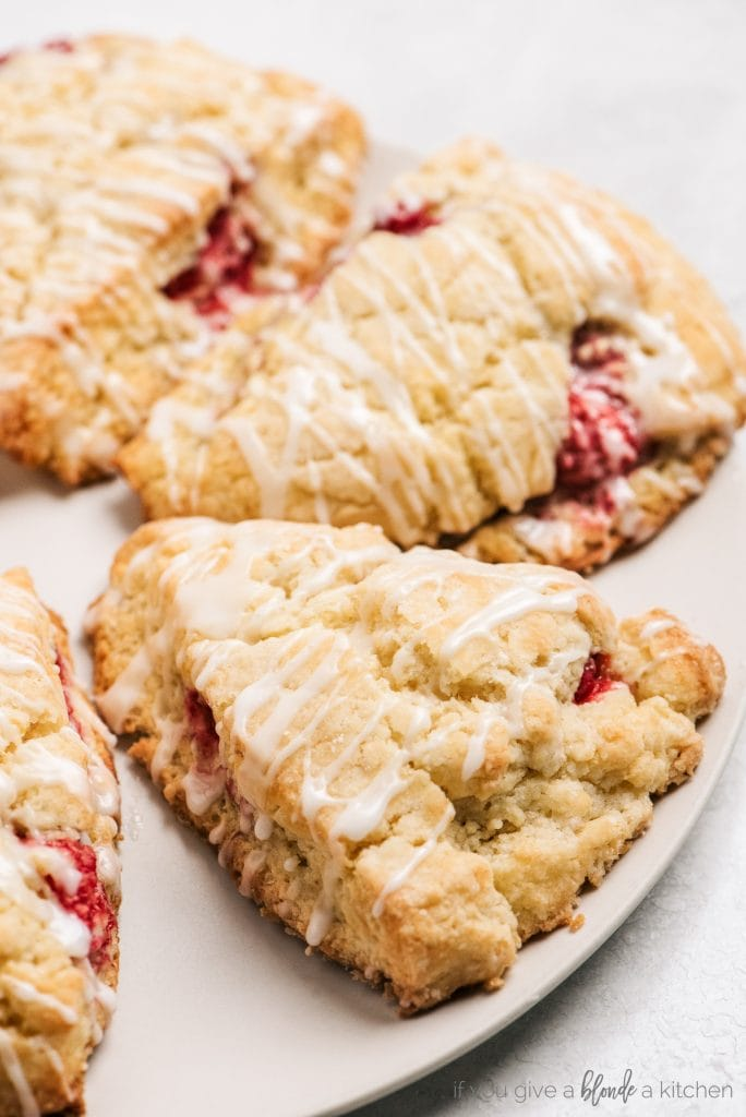 lemon raspberry scones with glaze on white plate