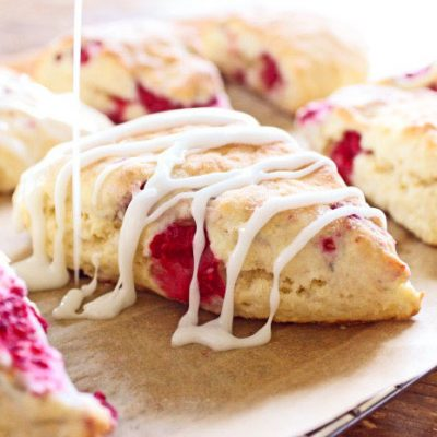Lemon raspberry scones on parchment paper with icing drizzle on top