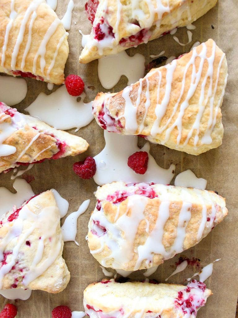 raspberry scones on parchment paper with lemon glaze drizzled on top