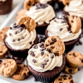 plate of cookie dough frosting cupcakes topped with mini chocolate chips and mini chocolate chip cookies