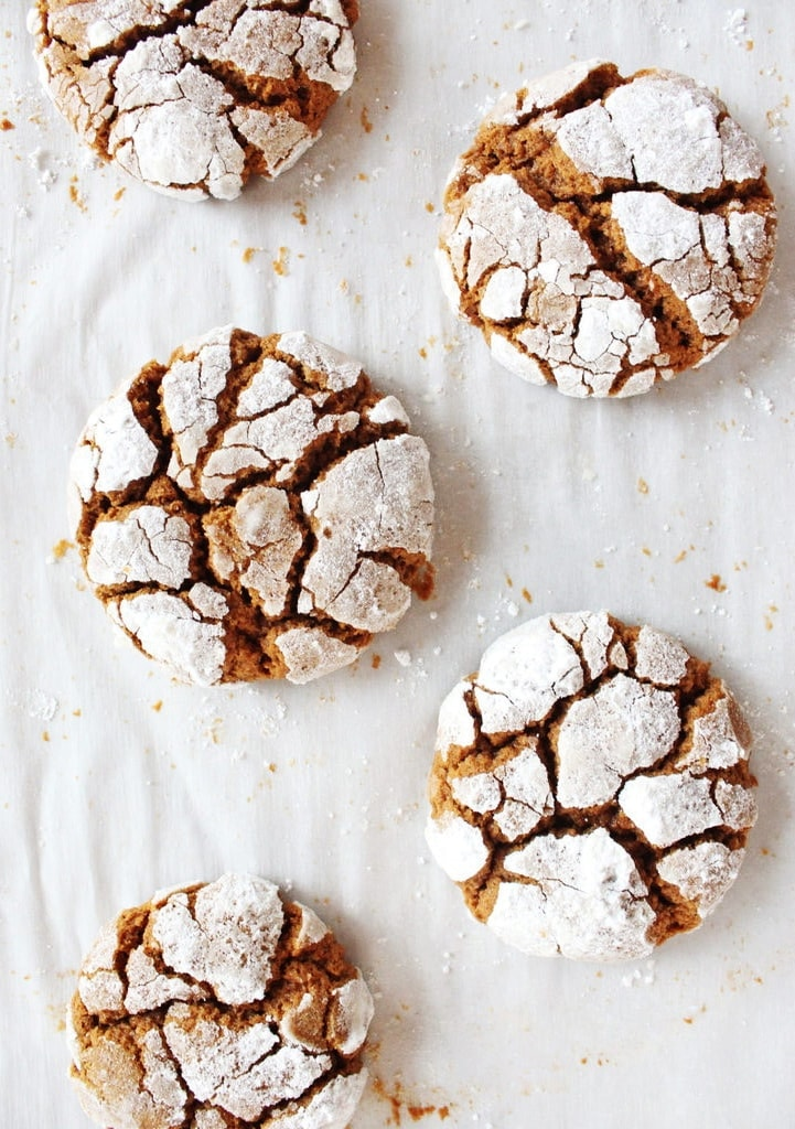 Christmas Gingerbread Crinkle Cookies on parchment paper with powdered sugar