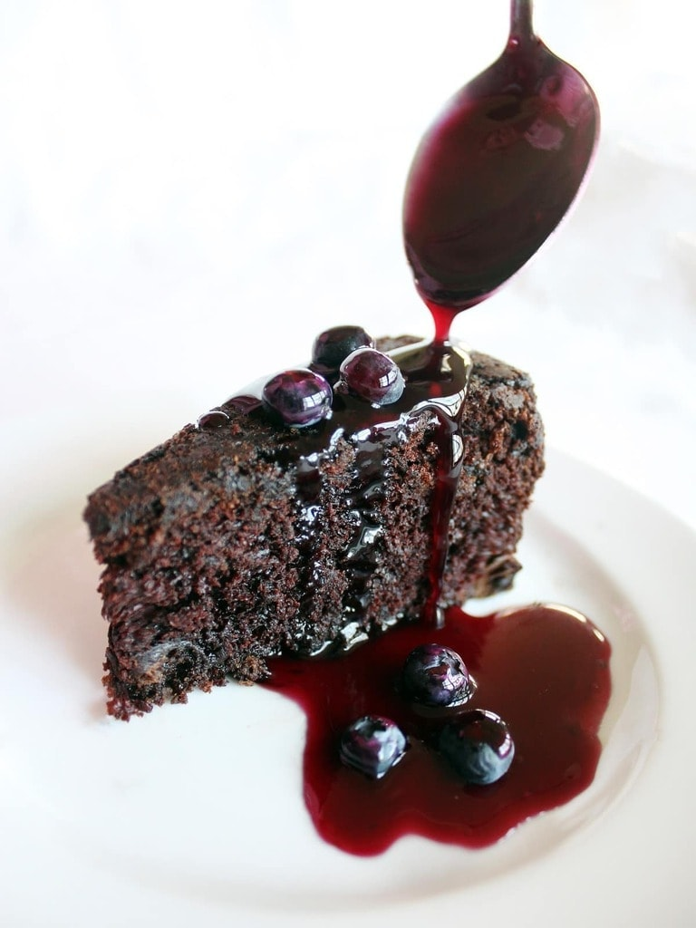 The delicious chocolate cake is sweetened with blueberries in and on the cake. The blueberry sauce is not only delicious on the cake, but on ice cream too!| Recipe by @haleydwilliams