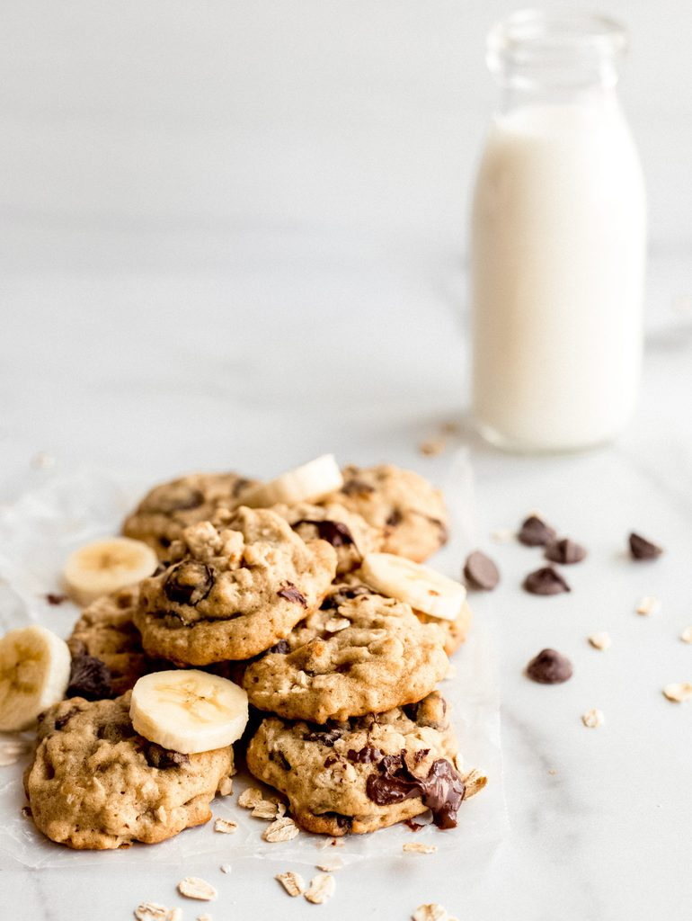 banana oatmeal cookies in pile with banana slices. Glass bottle of milk
