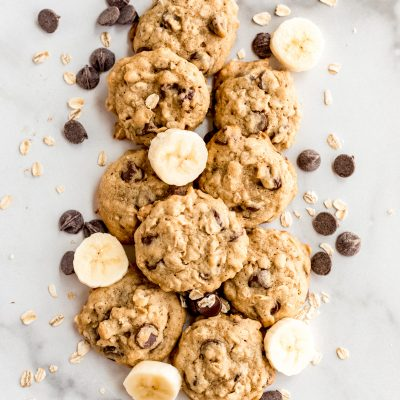 banana oatmeal cookies on parchment paper with slices of banana, chocolate chips and oats