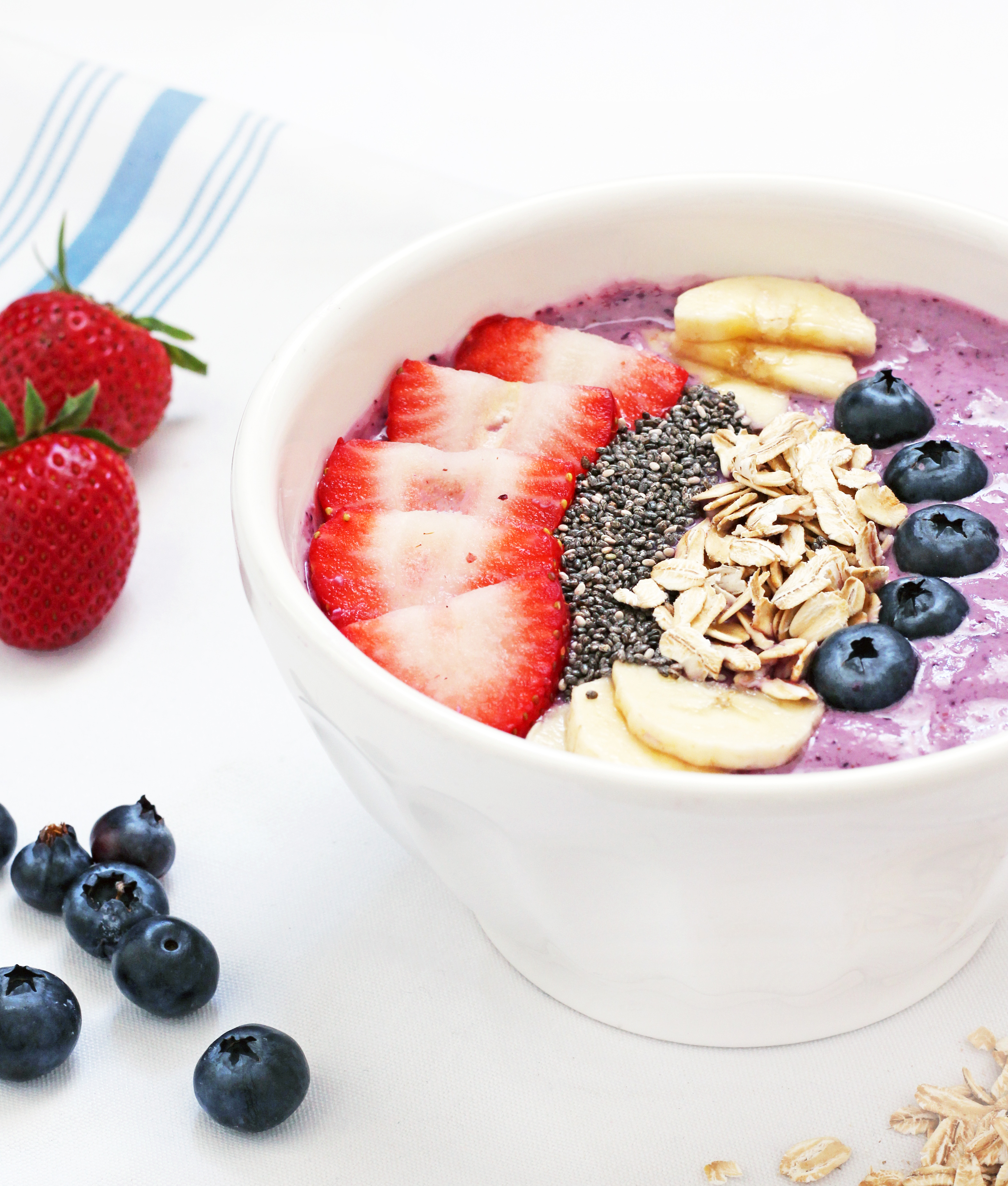 The Berry Banana Smoothie Bowl recipe is a blend of blueberries, strawberries, banana, yogurt and oats. It's pleasing to the eye and your tastebuds! | Recipe by @haleydwilliams