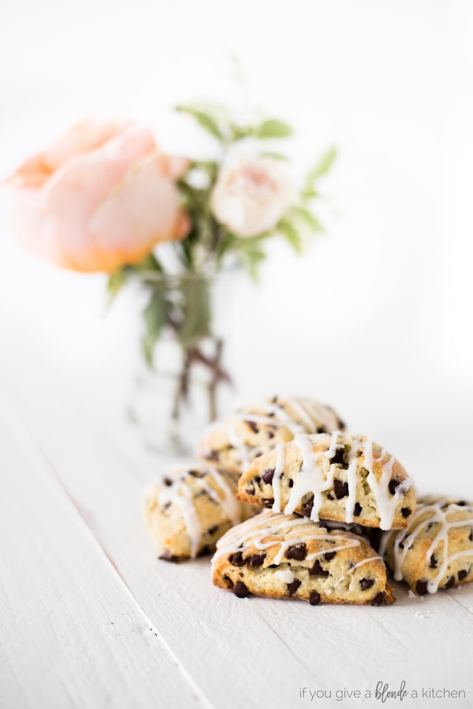 two bite chocolate chip mini scones pile with pink flowers in the background