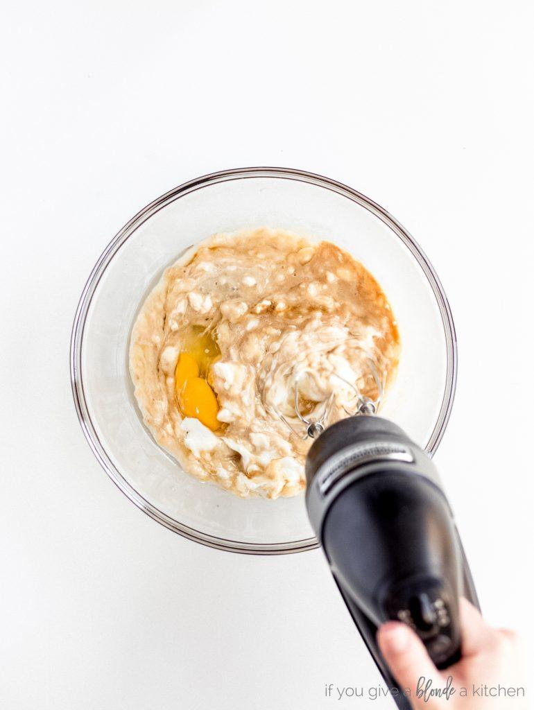 hand mixer combining ingredients in glass bowl