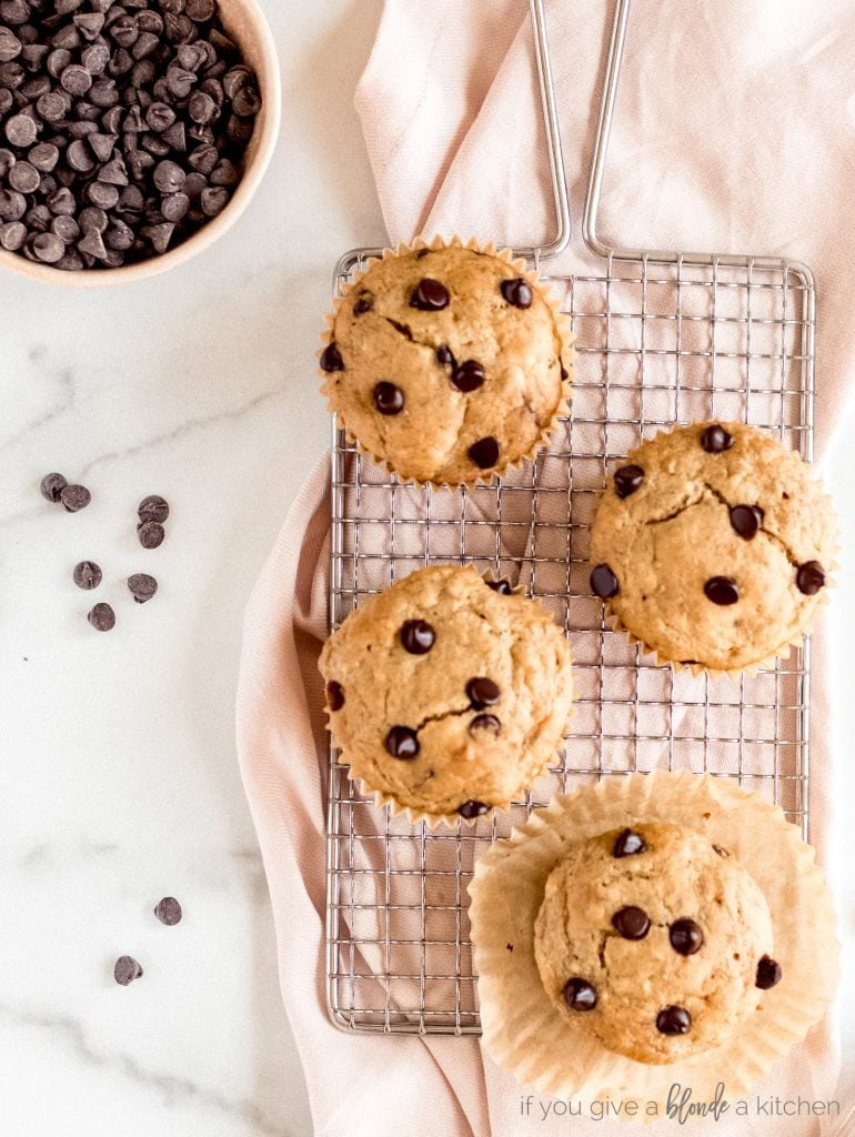 banana chocolate chip muffins on cooling rack and pink kitchen towel bowl of chocolate chips