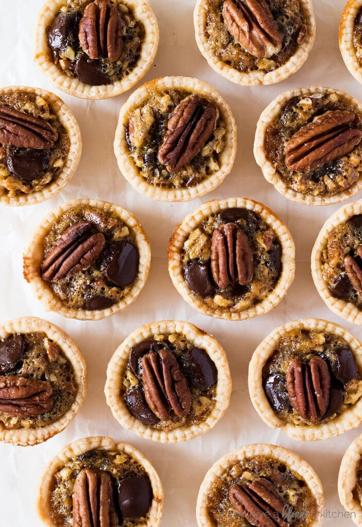 Mini Kentucky derby pies in pie shells with pecan halves on top. Geometric display on white wooden table