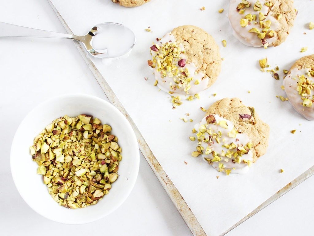 Iced pistachio oatmeal cookies uses your basic chewy oatmeal cookie recipe with pistachios mixed into the batter and sprinkled on top of the icing. Delicious! | www.ifyougiveablondeakitchen.com