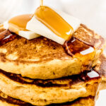 syrup on top of butter pads on pumpkin pancake stack