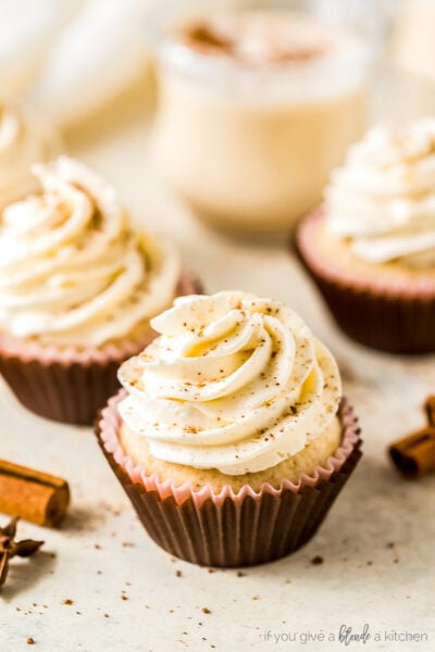 eggnog cupcake in brown paper liner; eggnog frosting dusted with nutmeg