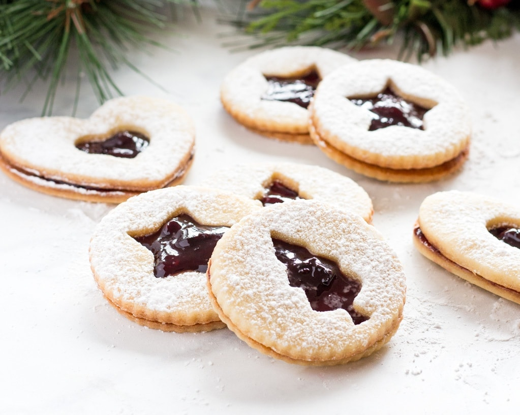 Holiday linzer cookies are filled with fruit jam spread and dusted with confectioners' sugar.