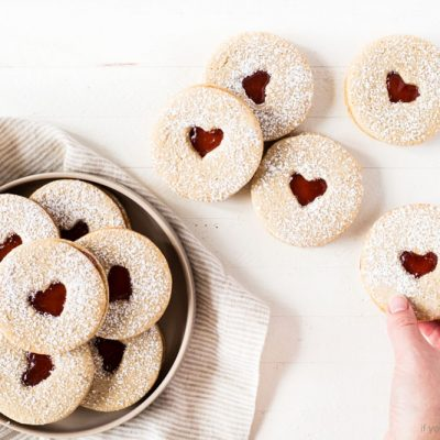 Linzer cookies with heart for Valentine's Day. Raspberry jam and confectioners' sugar. Cookie on plate withkitchen cloth