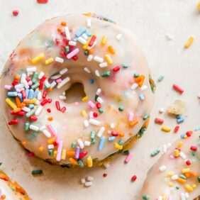 baked birthday donuts topped with glaze and rainbow sprinkles