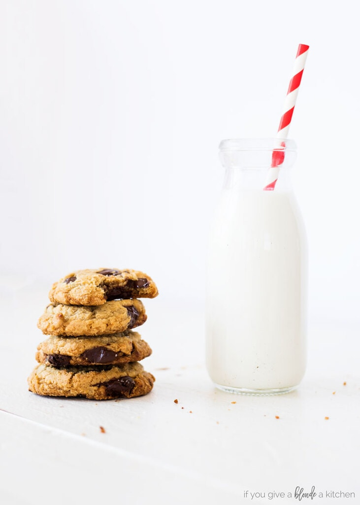 homemade chocolate chip cookies stack of cookies with glass of milk with red stripe straw