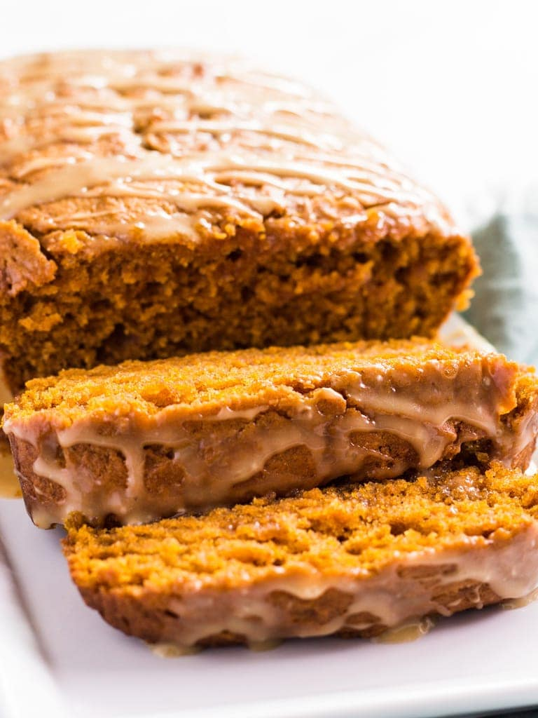 Pumpkin bread with maple glaze is filled with fall spices. Each slice is moist and tastes amazing. Try this easy recipe and share with friends! | www.ifyougiveablondeakitchen.com