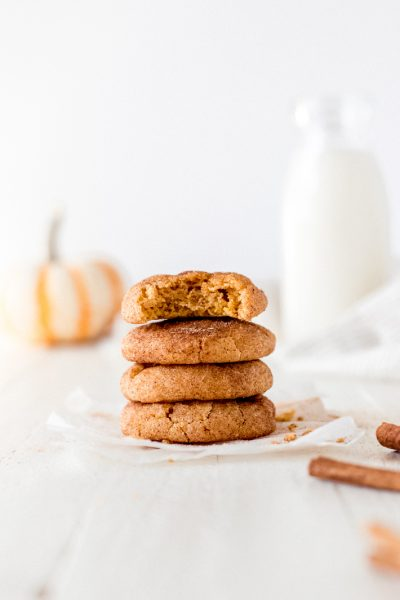 pumpkin snickerdoodle cookies stack with bite and glass milk bottle