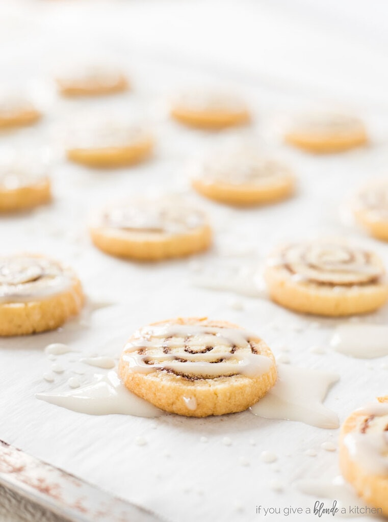 Cinnamon roll cookies on baking sheet and parchment paper with icing