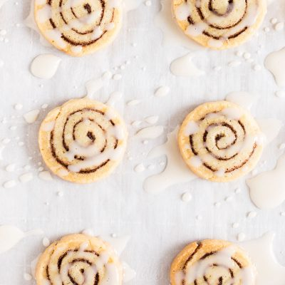 Cinnamon roll cookies on parchment paper with icing