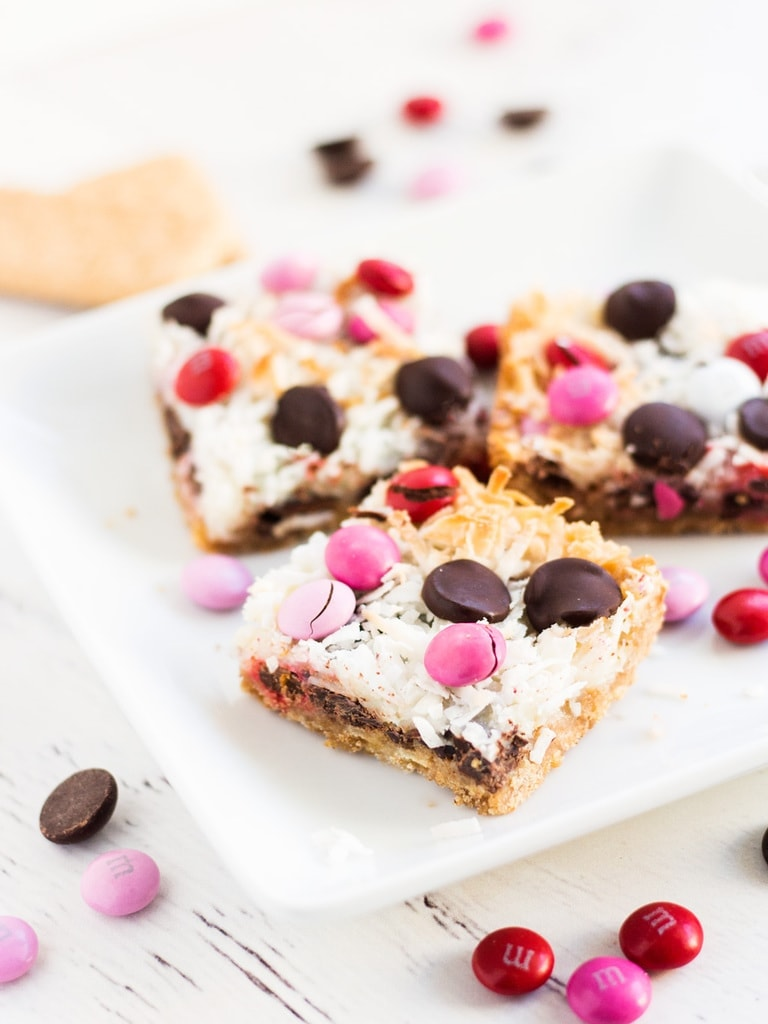 Use this M&M magic cookie bars recipe for Valentine's day. The coconut gets nice and toasted while the chocolate chips and M&M's melt. They're a simply delicious dessert! | www.ifyougiveablondeakitchen.com
