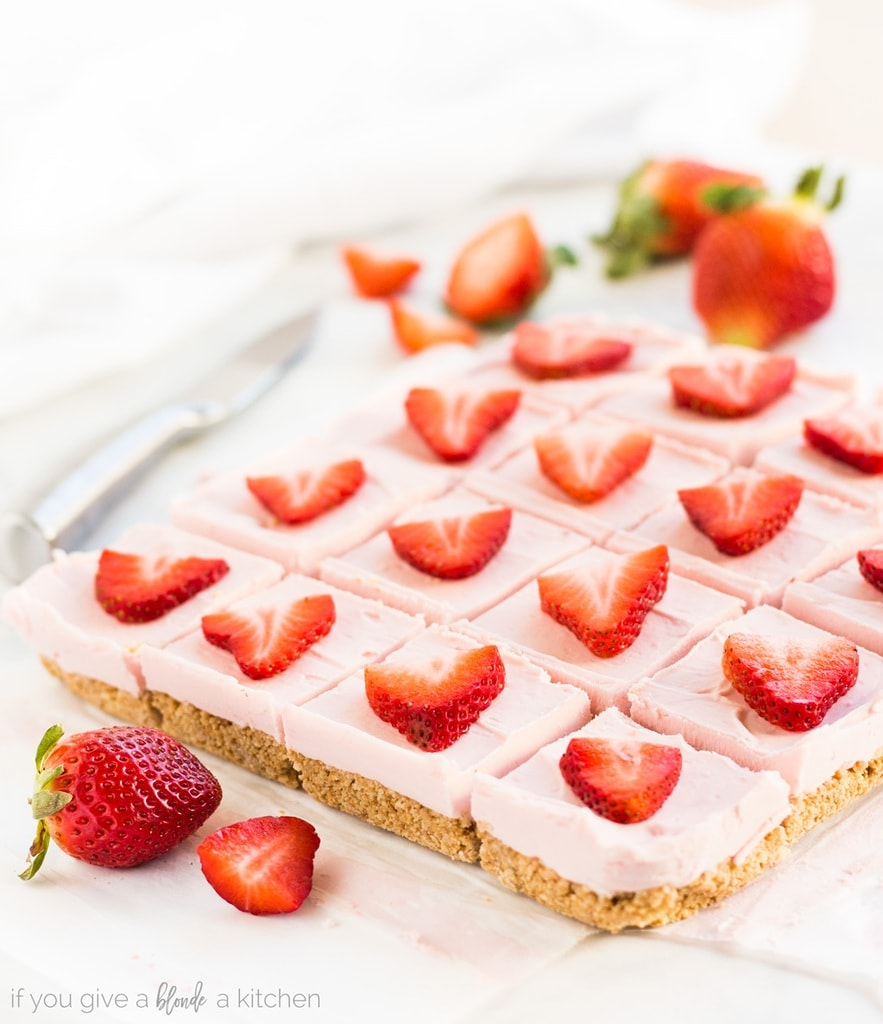 No bake strawberry cheesecake bars are an easy dessert to make. The recipe calls for graham crackers, butter, confectioners' sugar, cream cheese, vanilla and strawberries. | www.ifyougiveablondeakitchen.com