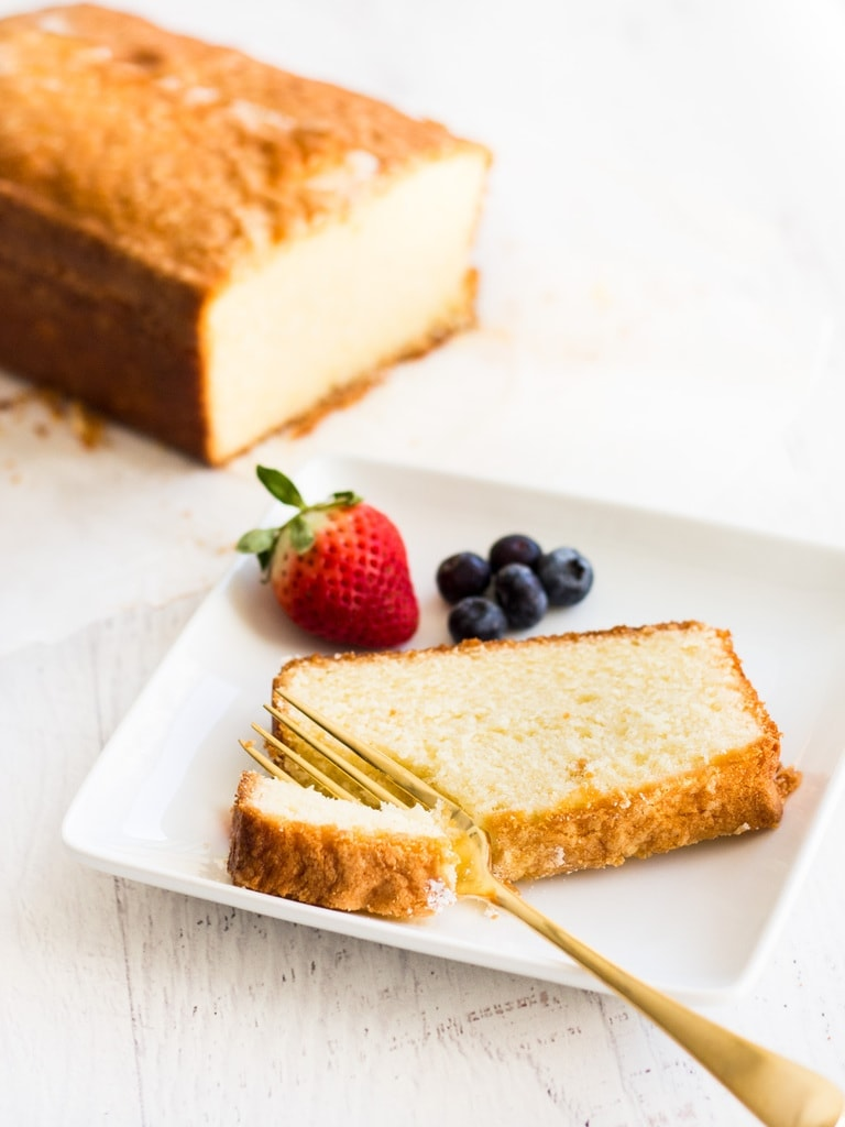 Best pound cake recipe slice of cake with gold fork and fruit