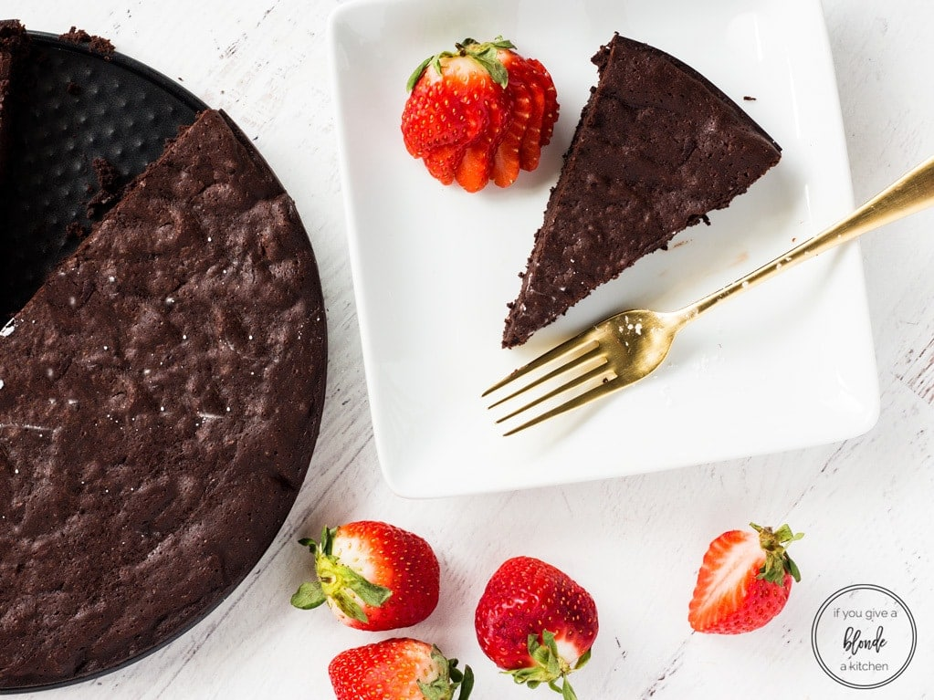 Easy flourless chocolate cake slice with strawberries and gold fork