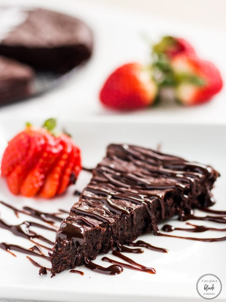 Easy flourless chocolate cake slice with chocolate drizzle and strawberries