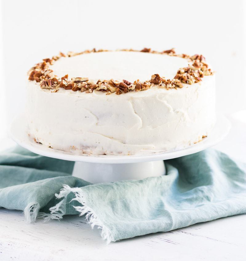 Homemade carrot cake recipe on a cake pan with a blue cloth