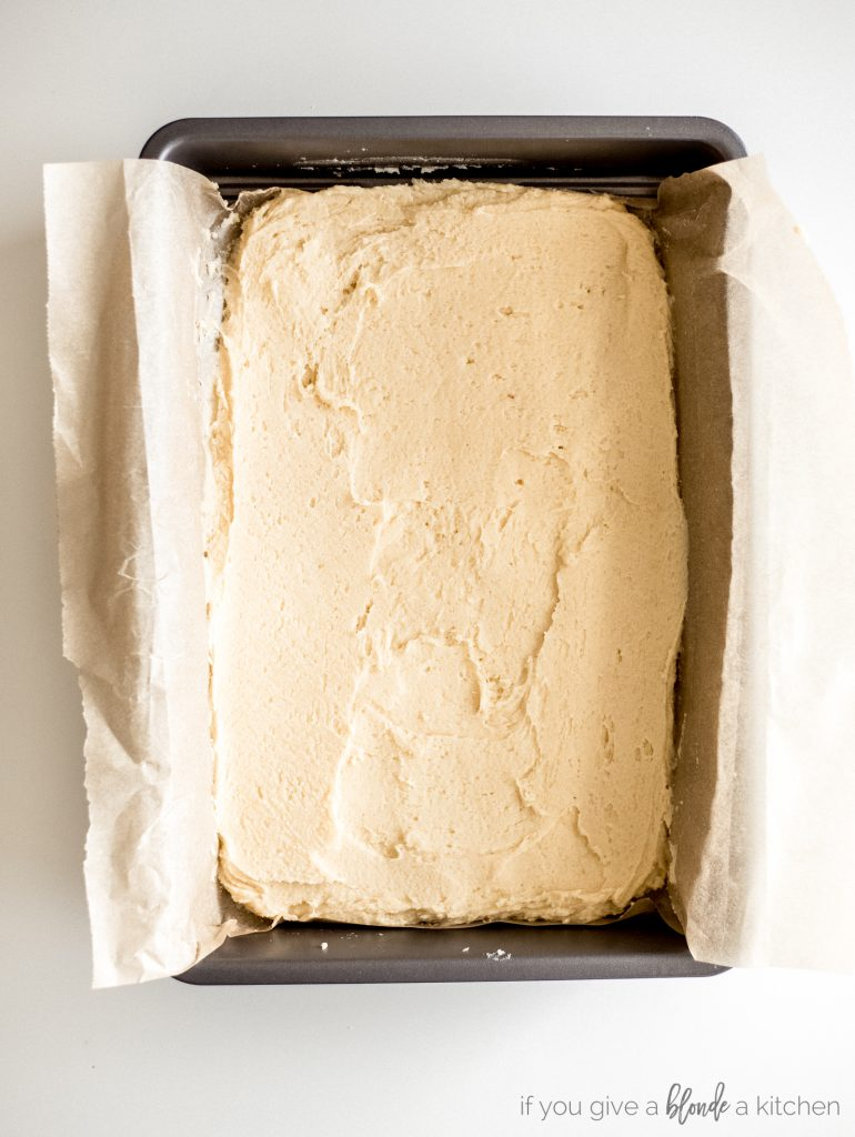 sugar cookie bar dough in 9x13 pan with parchment paper