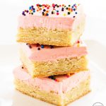 Stack of sugar cookie bars with pink frosting and sprinkles