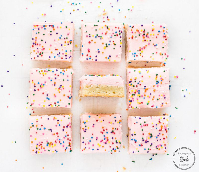 Sugar cookie bars recipe with pink frosting and sprinkles cut into squares
