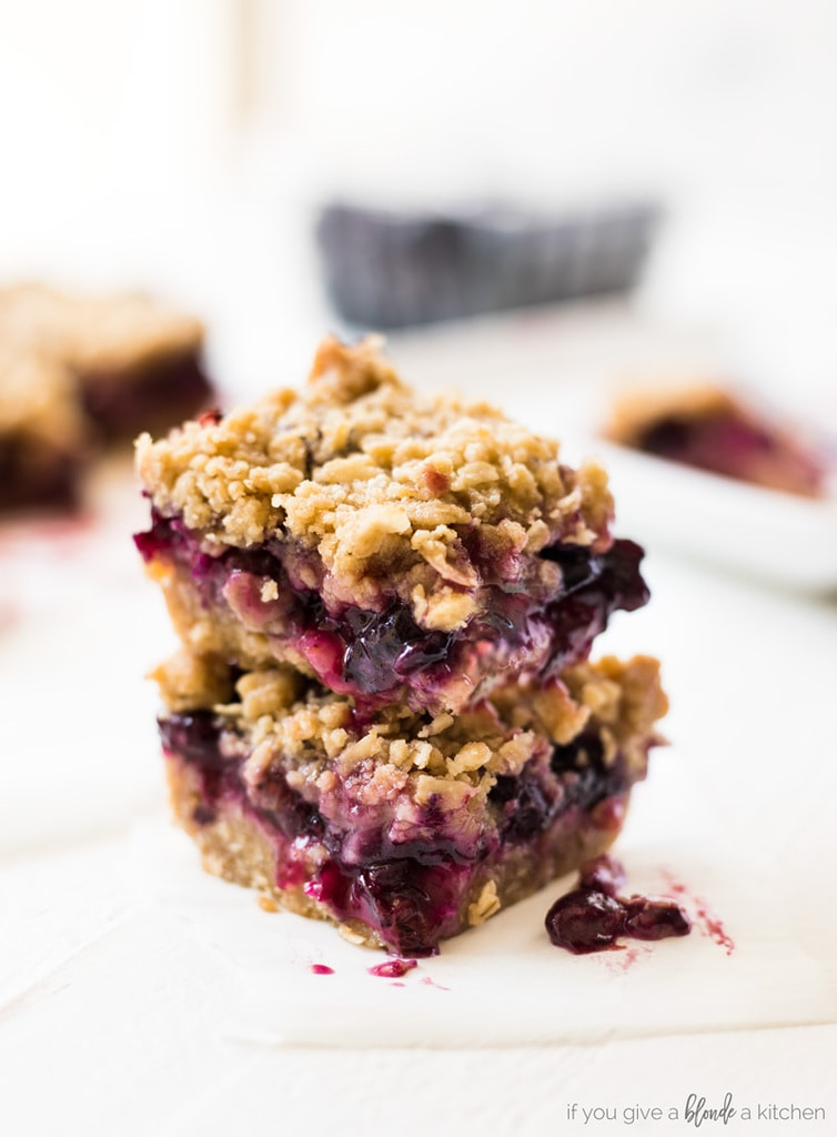 blueberry crumble bars stacked on top of each other with blueberry filing