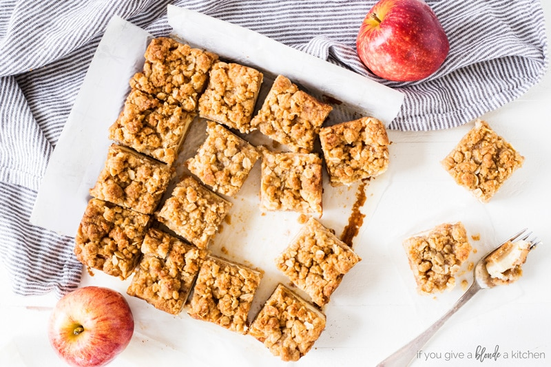 apple cheesecake bars cut into squares with apples, parchment paper and striped kitchen towel