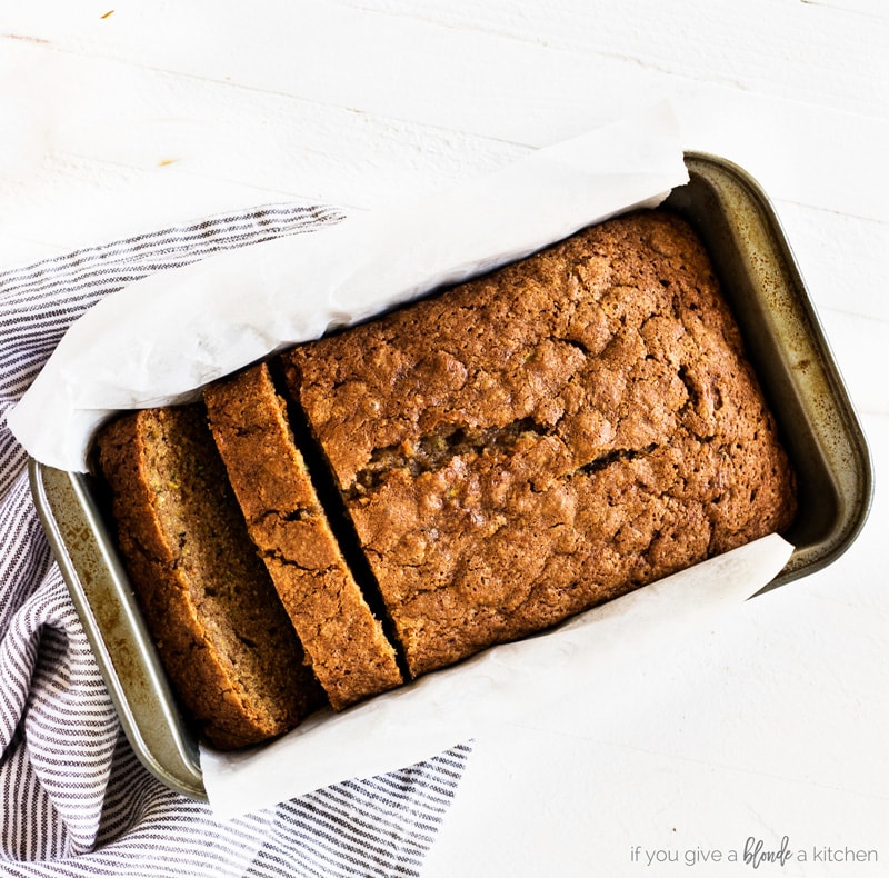 Moist zucchini bread recipe in loaf pan with cloth and parchment paper