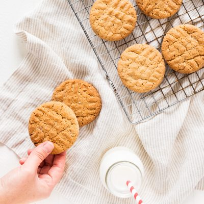Classic peanut butter cookie recipe with fork cross hatch, cooling rack and glass bottle of milk