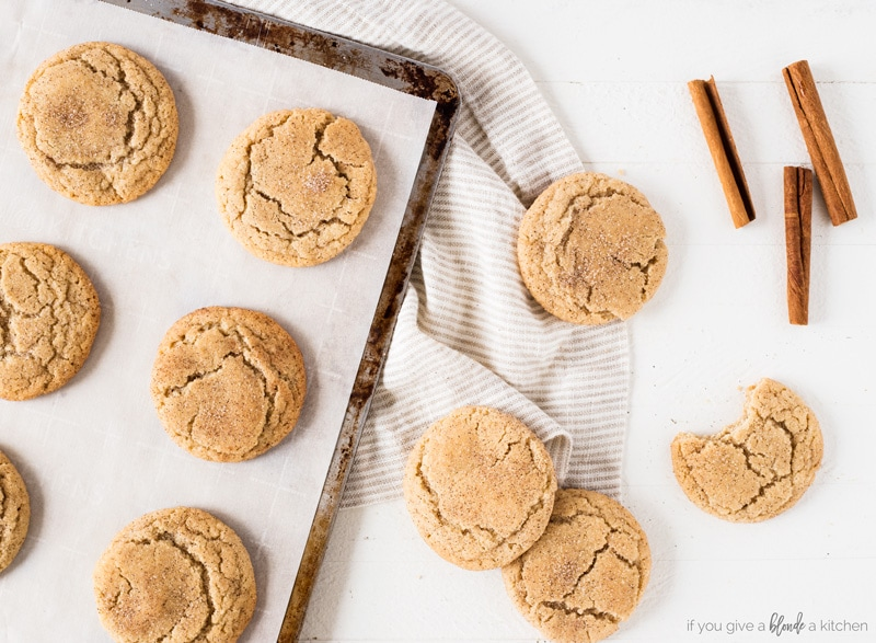 Homemade snickerdoodle cookies recipe on cookie sheet with kitchen towel and cinnamon sticks