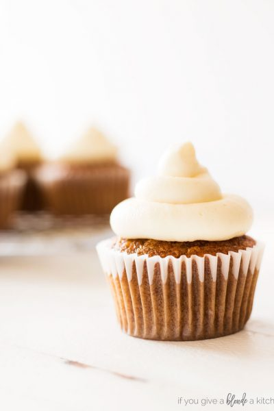 Carrot cake cupcakes with cream cheese frosting. Orange cupcake with off white frosting in white wrapper with white background